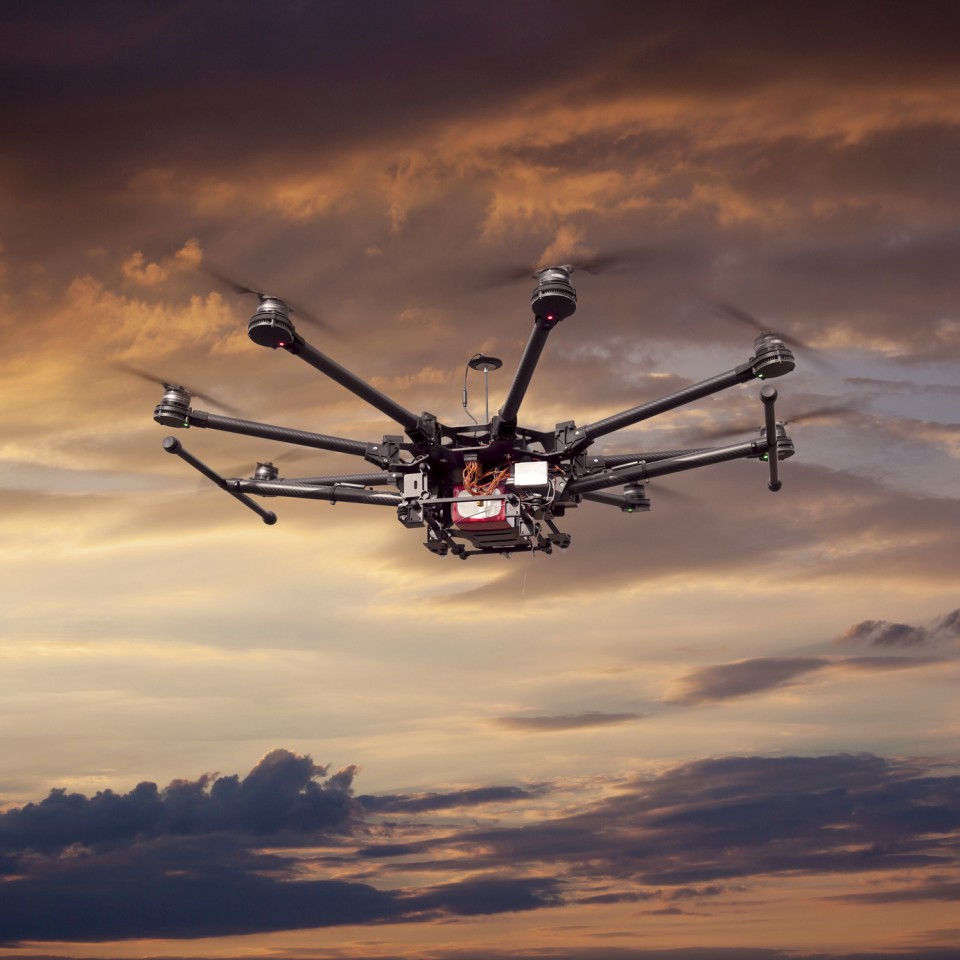 Flying copter with their gear on the background of a beautiful sunset.