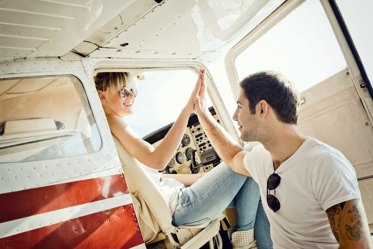 men and woman high-fiving in a small aircraft