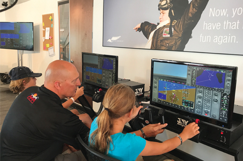 Instructor and student using flight simulator technology on computers