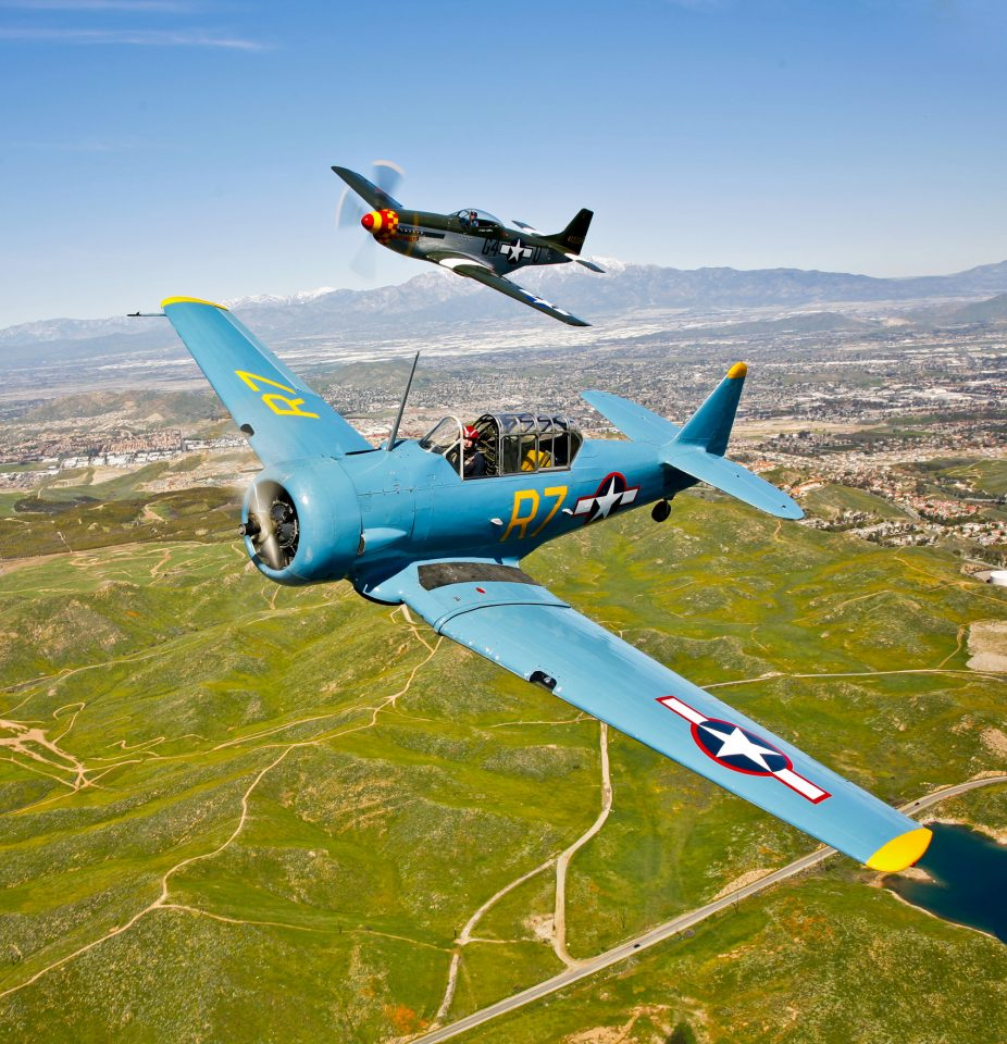 A North American T-6 Texan and a P-51D Mustang in flight over Chino, California.