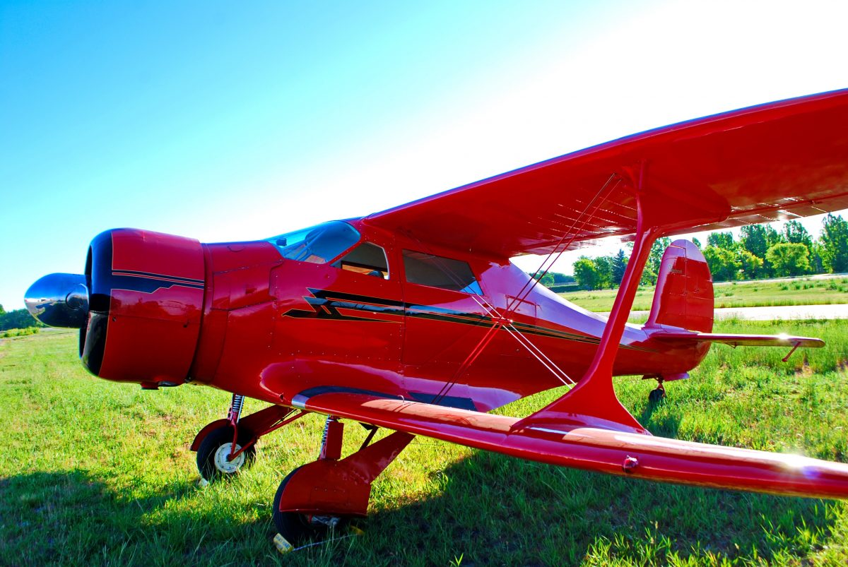 Red Beechcraft Staggerwing aircraft parked in grass runway in Idaho