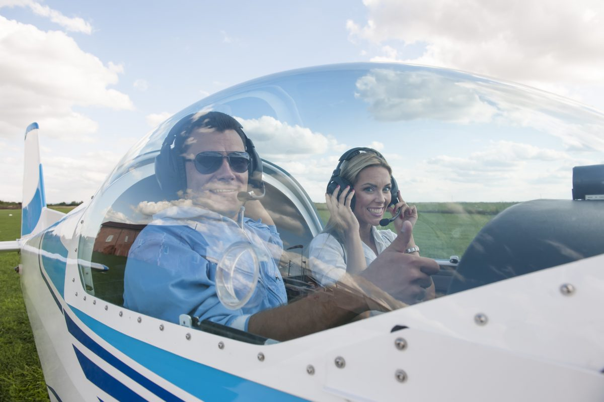 Woman and man pilot looking at camera, showing thumb up, preparing for flying