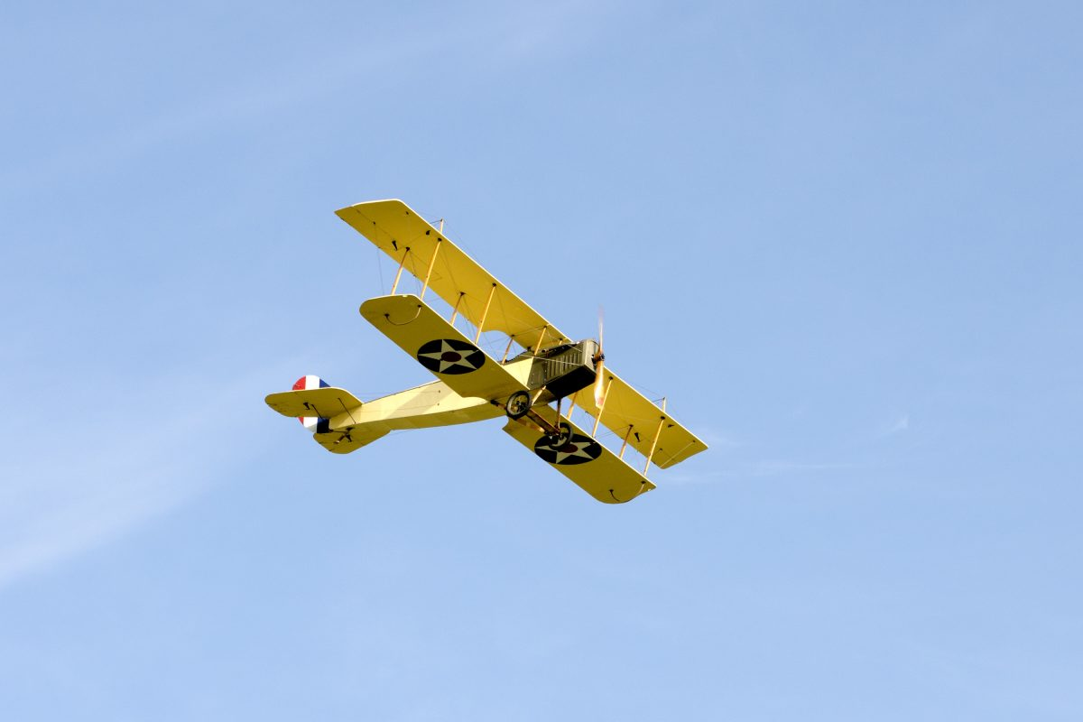 Flying Curtiss JN-4H biplane in Army Air Service colors of blue and yellow.