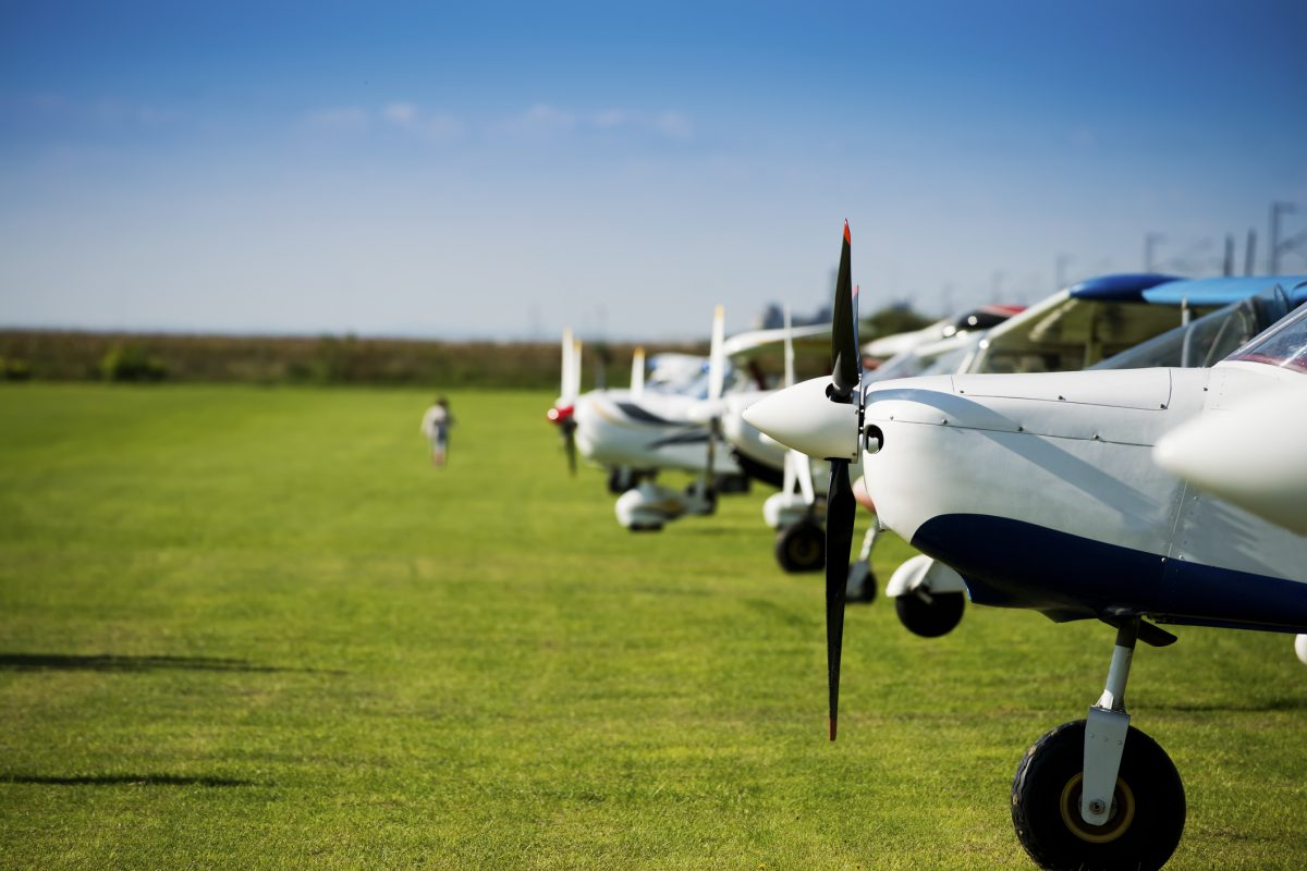 Small sports airplanes in a row on field