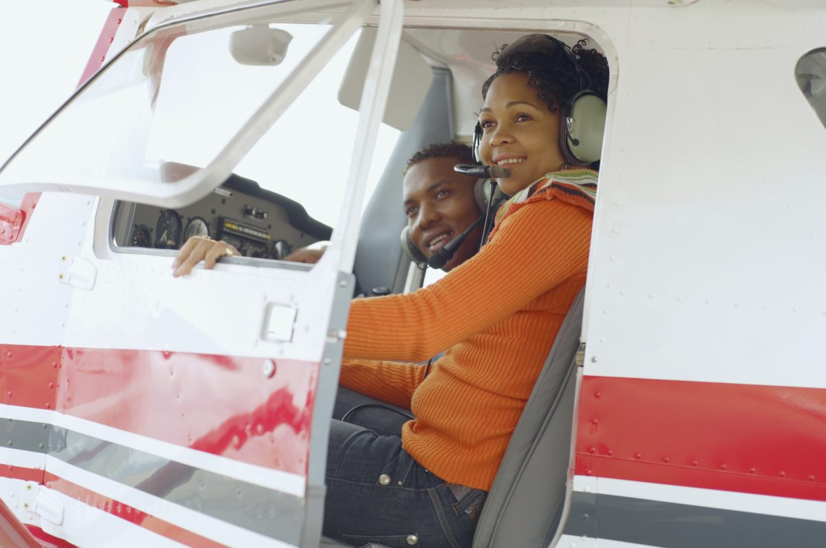 African American couple sitting in cockpit of small airplane