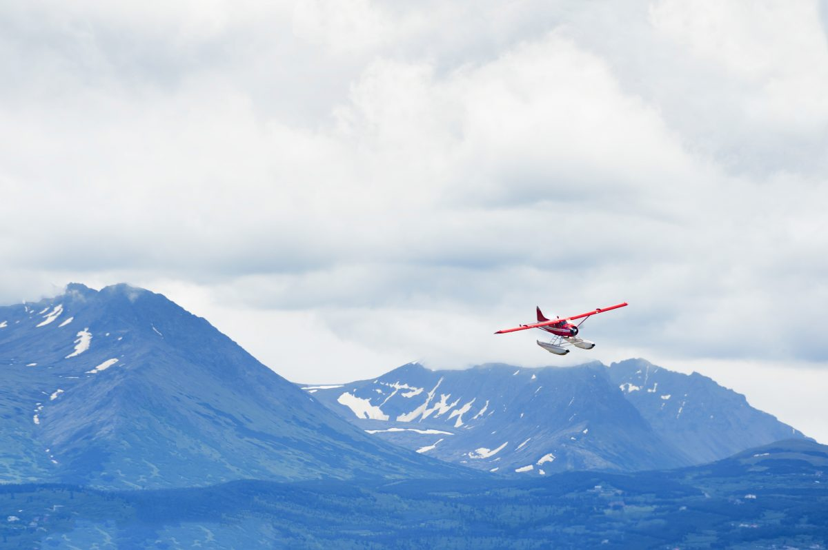 Chugach Mountain range under cloudy skies provides a majestic back drop to a seaplane as it prepares to land at Lake Hood in Anchorage, Alaska.
