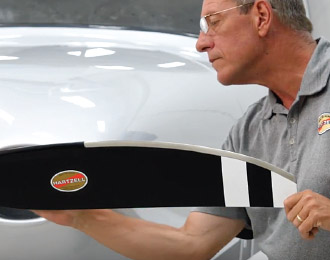 Hartzell Propeller technician Kevin Ryan examining black and white Hartzell propeller blade