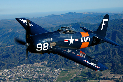 Blue and orange F8F Bearcat aircraft flying over Chino, California
