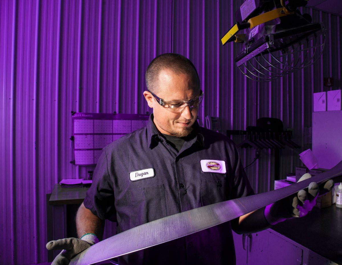Hartzell employee holding propeller blade in factory