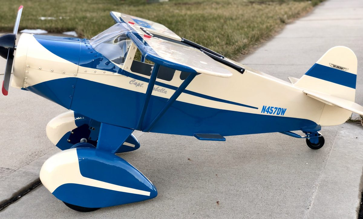 Blue and white Taylorcraft Pedal Plane facing sideways on the ground