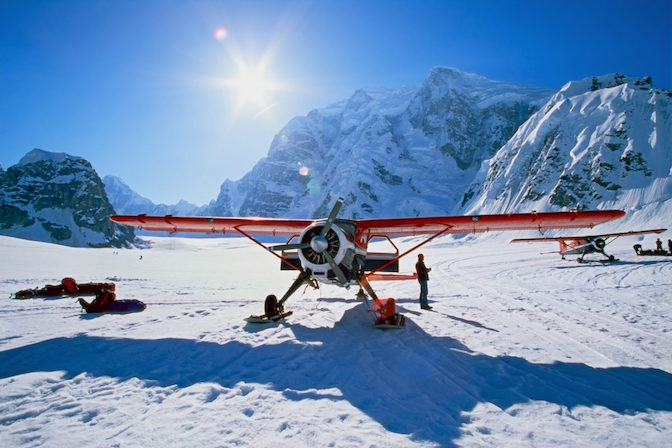Propeller-driven airplane in a snowy mountainous area.